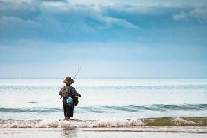 潮時の意味を考えながら釣りをしている男性