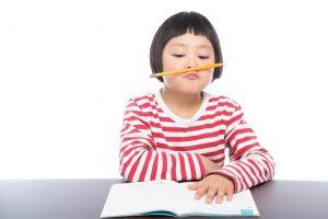 鉛筆の濃さについて考えている少女